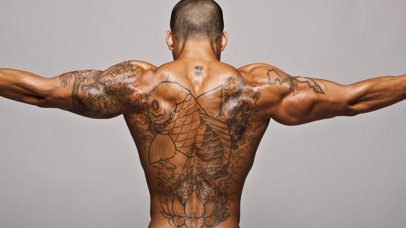 Накаченный мужчина с тату на спине