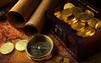 Золотые монеты и компас на карте